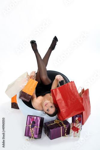 Woman in chair holding shopping bags