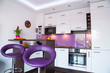 Modern living room interior with white and purple kitchen
