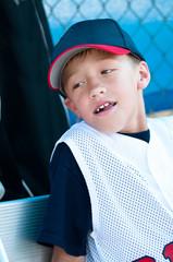 Little league baseball player in dugout