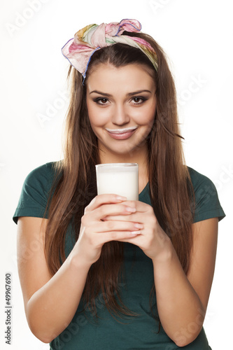 girl in a green shirt with a pleased gesture drinking milk