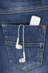 MP3 player and earphones sticking out of jeans pocket
