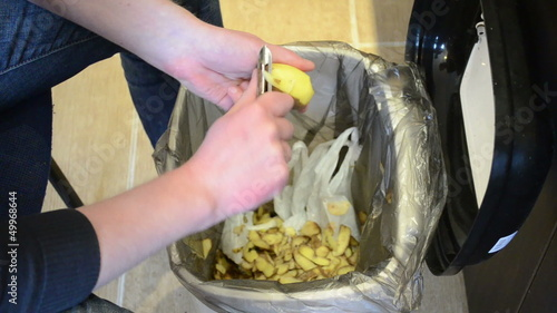 man hands peel potato. paring fall into waste bin