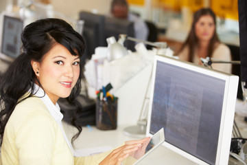 Woman Using Digital Tablet In Busy Creative Office