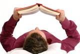 Hombre joven recostado leyendo un libro.