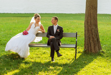 The couple sitting on a bench in the park