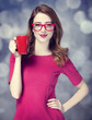 Redhead girl with red cup.