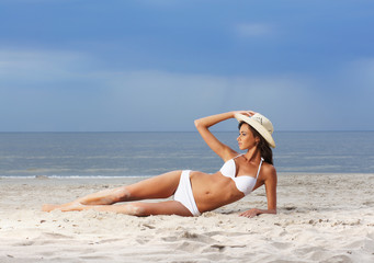 A young woman in a white swimsuit and a hat on the beach