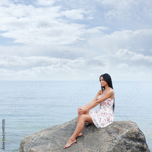 A young and beautiful brunette woman in a dress near the sea