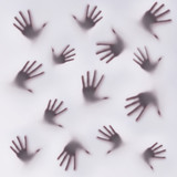 Frightening silhouettes of many hands on a foggy glass