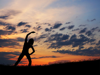 Silhouette of a young woman doing an exercise on a sunset