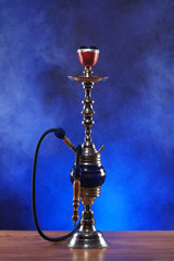 An old ceramic hookah on a dark blue and foggy background