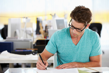 Man Writing At Desk In Busy Creative Office