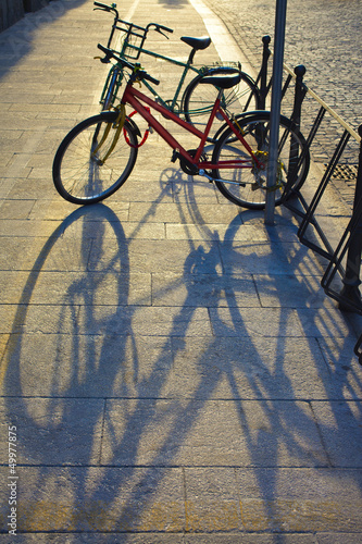 two bicycles in a rack on the sidewalk
