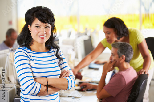 Portrait Of Woman Standing In Busy Creative Office