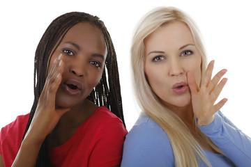 Schwarze und weiße Frau rufen laut - mit Händen am Gesicht