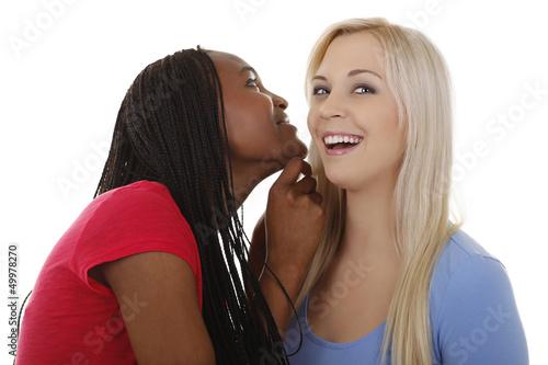 Schwarze Frau sagt weißer Frau etwas ins Ohr