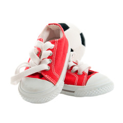 Red baby sneakers with a ball isolated on white