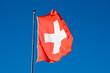 The swiss flag waving in front of a deep blue sky
