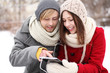 Winter couple with digital tablet