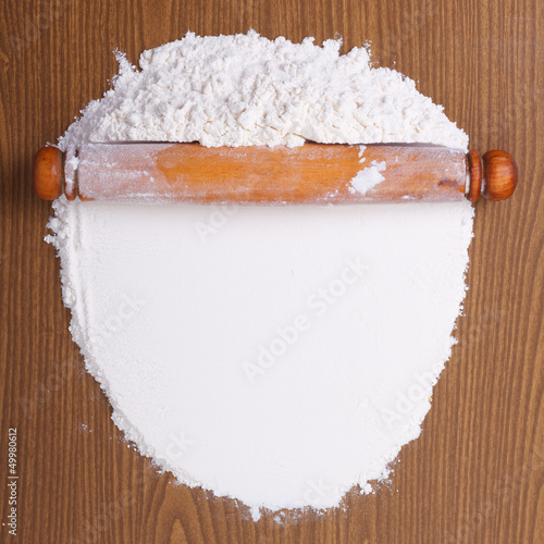 Wooden rolling pin with white wheat flour on the table. top view