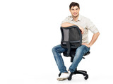 Portrait of smiling happy man sits on office chair