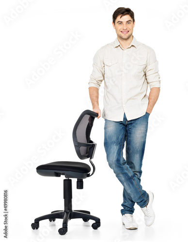 happy man stands near the office chair