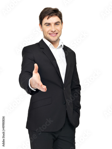 Smiling businessman in black suit gives handshake