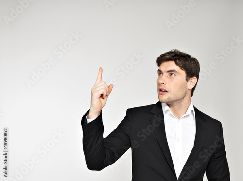 Happy businessman points his finger up