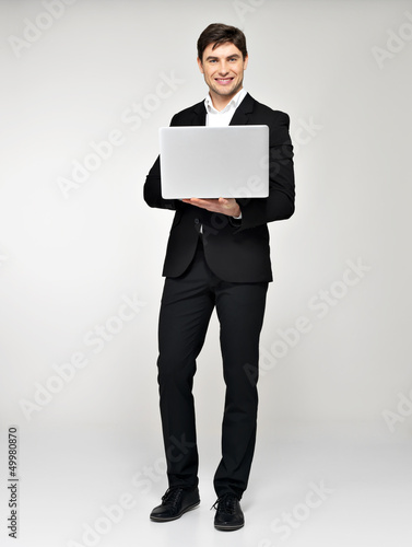Full portrait of young man with laptop  in casuals