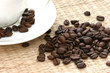 Whole coffee beans scattered on straw background with white cup