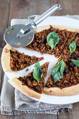 Meat pizza with basil, raisins, and olives