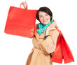 Happy woman with shopping bags in beige autumn coat