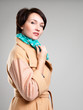 Beautiful woman in autumn coat with green scarf