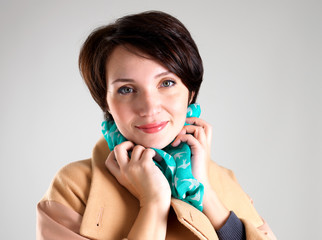 Happy woman in autumn coat with green scarf