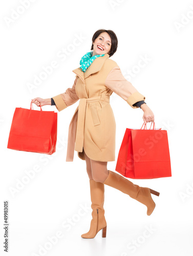 Portrait of happy woman with shopping bags in autumn coat