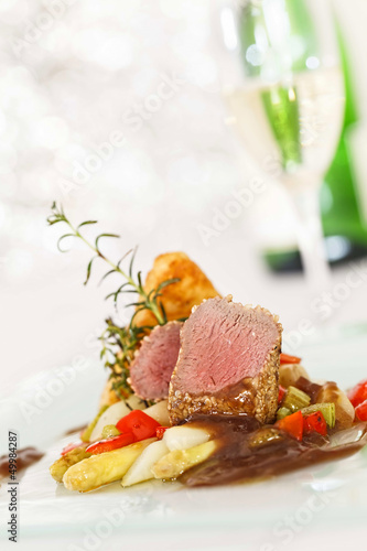 Roasted saddle of lamb on asparagus ragout and herbs