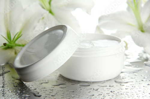 Cosmetic cream and beautiful lily, close up