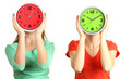 Girls holding clocks over face isolated on white