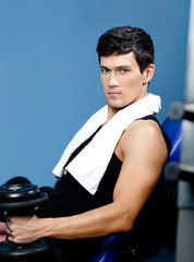 Athletic man in sports wear rests handing a weight