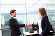 Business handshake at modern office with bussiness people on bac