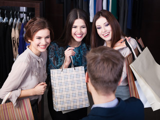 Girls consult with shop assistant concerning buying presents