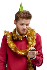 Disappointed man with tinsel holds small cake with candle
