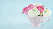 Ranunculus flowers in a pink cup with copy space