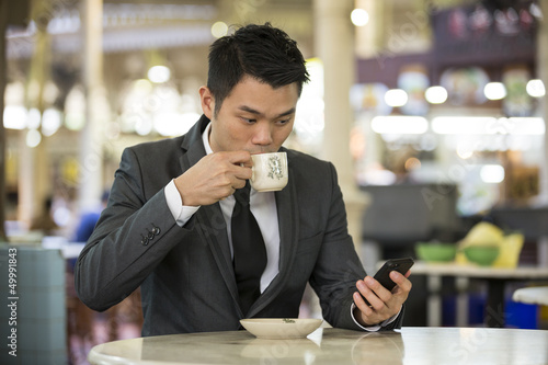 Chinese business man in a food court using his phone.