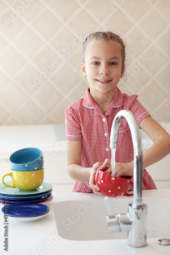 Little girl washing the dishes