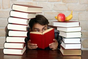 Mann schaut auf gesundes Obst auf Büchern
