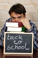 "Leser mit Stapel Büchern, Schild ""back to school"""