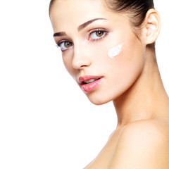 Beautiful face of young woman with cosmetic cream on a cheek.