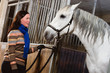 Woman and white horse inside a stall, horizon format