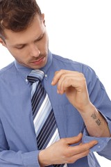 Young businessman with tattoo in forearm